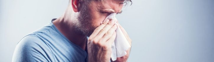 Man blowing nose due to allergies.