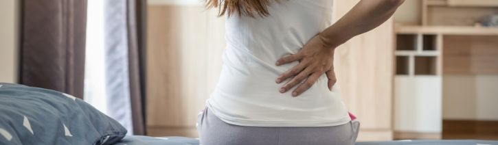 Woman sat on a mattress with back ache.
