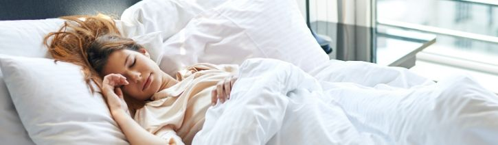 Woman sleeping cool in breathable and dry bed sheets.