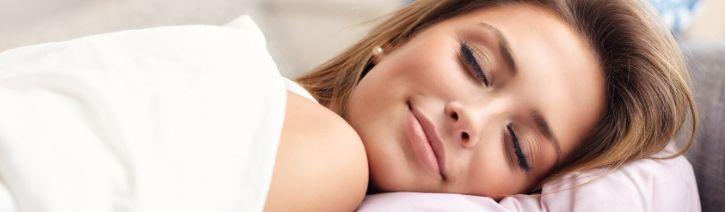 Woman sleeping on a silk bed sheet.
