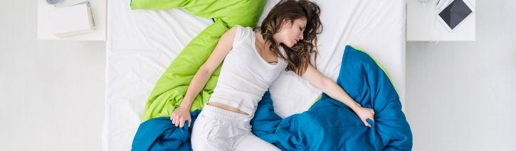 Woman too hot in her bed due to night sweats.