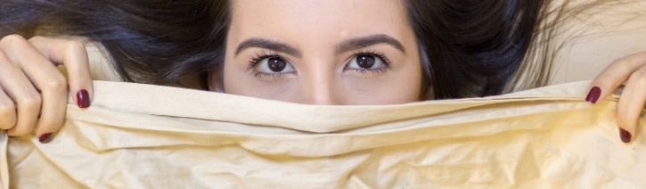 Woman under a cooling flat bed sheet.