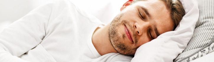 Man sleeping in luxury bed sheets.