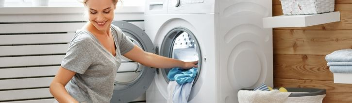 Woman putting satin bed sheets into the washing machine.
