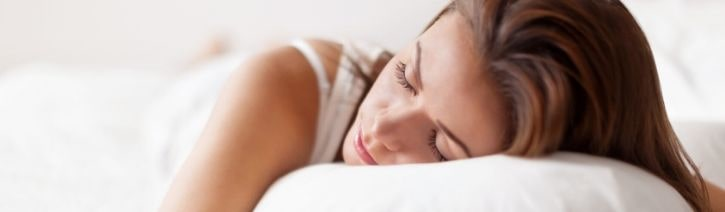 Woman sleeping on bamboo bed sheets and pillows.