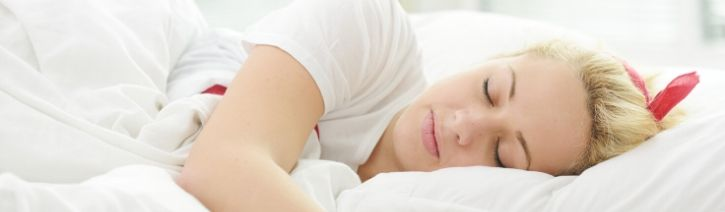 Woman sleeping on freshly washed bamboo bed sheets.