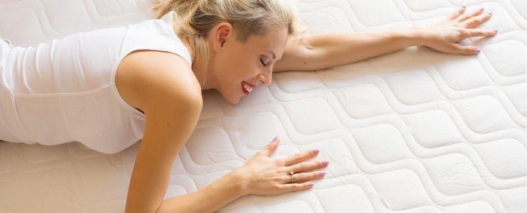 Woman rolling on a memory foam mattress.