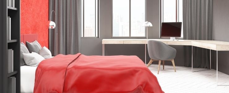 Red Bedding With Gray Walls and Red Accent Wall.