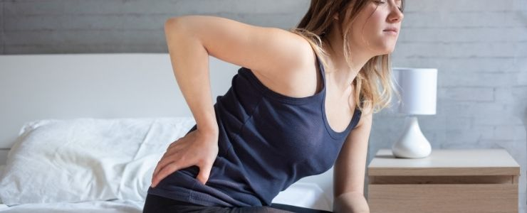 Woman With Hip Pain on a Mattress.